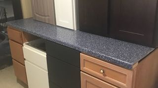 , The blue corian countertop is also salvaged and is simply resting atop the cabinets