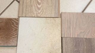, Big square in center is existing tile floor new bedroom laminate floor samples the one on the left the darker one is real wood floor and I m not using that but only for color which works the best actually so further homework