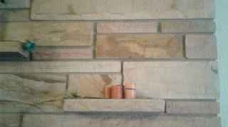 , Stone on wall surrounding fireplace which goes floor to ceiling