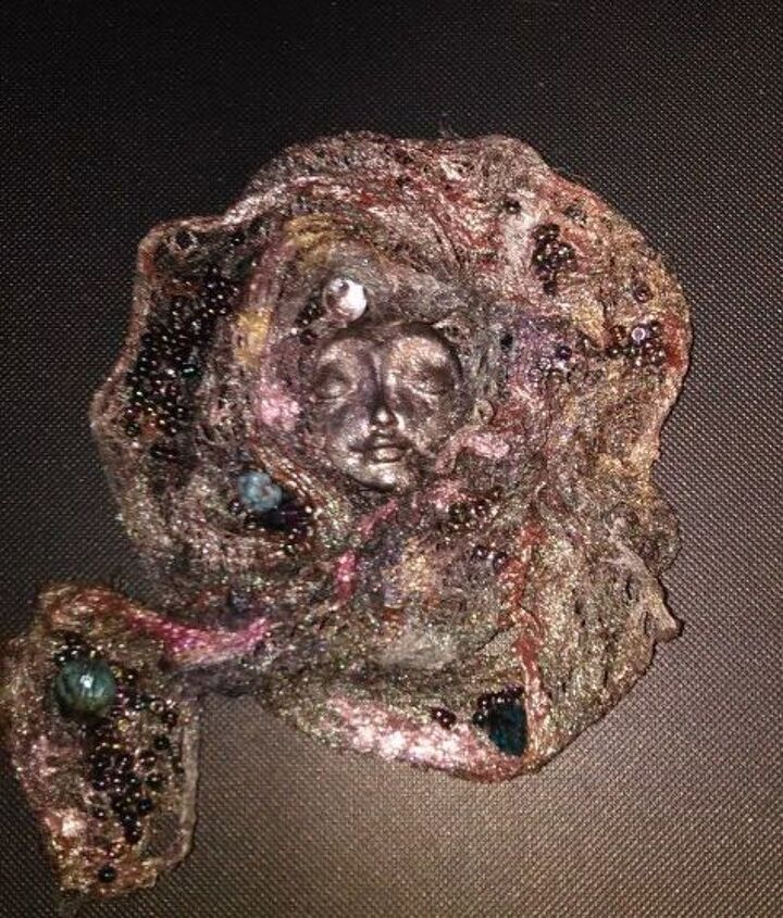 ethereal face of a woman on a brooch pin