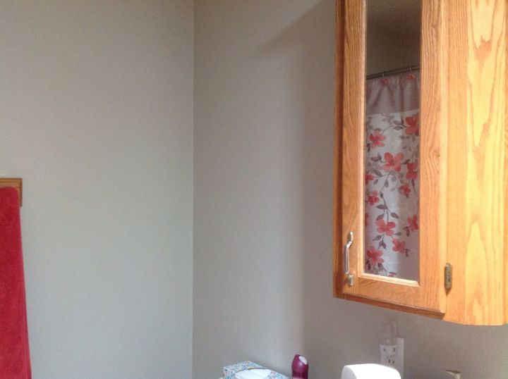 q how to decorate wall space above toilet beside honey oak vanity