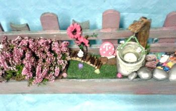a palette is transformed into a fairy garden with mushrooms and candle