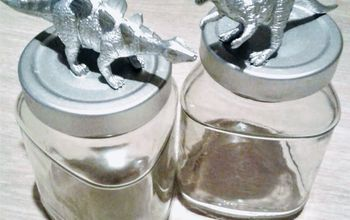 two silver dinosaurs on the lids of decorative jars