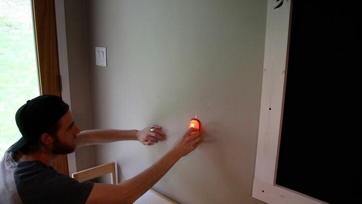 Using a stud finder to find the studs.