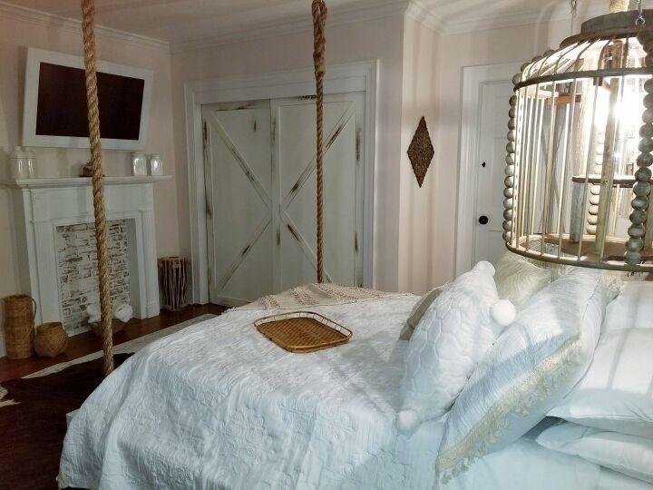 View of bed, mantle/tv & barn doors.