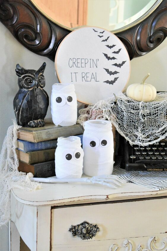 s 16 halloween decor ideas that ll be a huge hit at your party, Cute simple Halloween mummy jars