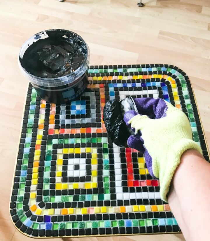 Add grout to tiles and work in gaps