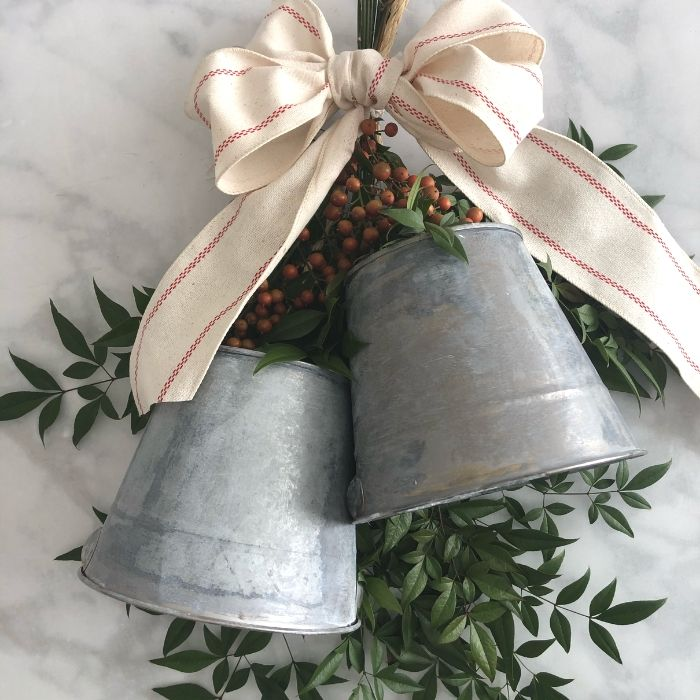 s 10 beautiful diy bells that will make your holiday home magical, Repurpose galvanized buckets into faux bell wreath
