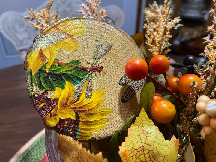 a decoupaged wood slice tucked into a fall arrangement