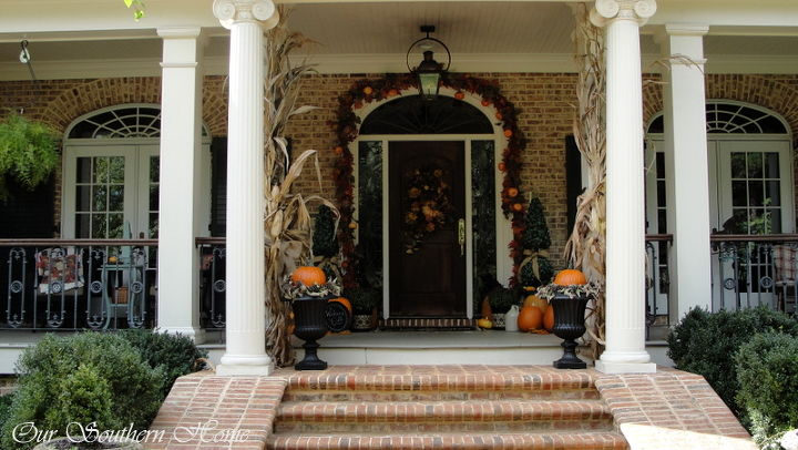 corn stalks from the local produce stand flank the entrance to the porch tied with burlap ribbon