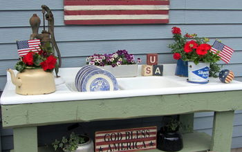 my potting bench has gone red white blue, flowers, gardening, outdoor living, A folk art flag sign USA Blocks and a God Bless America sign along with some miniature flags set a patriotic theme
