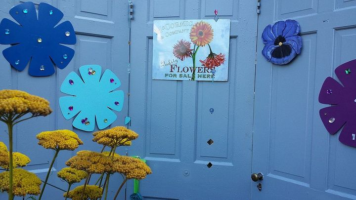 3 old doors painted and stand together creating a privacy fence and place to hang plaques and garden ornaments.