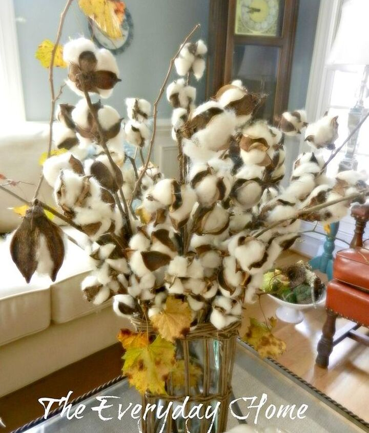 A willow and glass vase filed with good ole' Southern cotton and fresh grapevine.