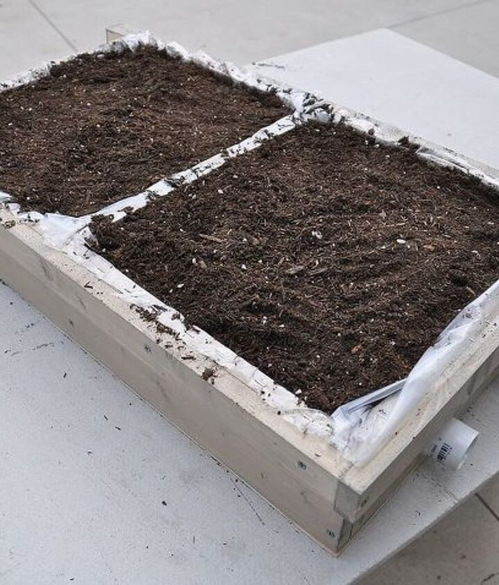Fill the vertical garden bed with dirt.
