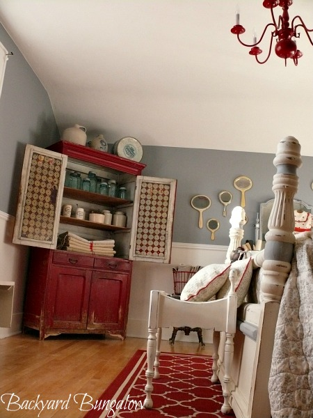 Rustic old red cabinet filled with European grain sacks, canning jars and marmalade crocks.