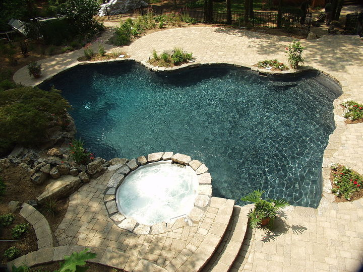Natural freeform gunite swimming pool with new spillover spa, mossrock waterfall, tumbled stone patio, landscaping. www.deckandpatio.com