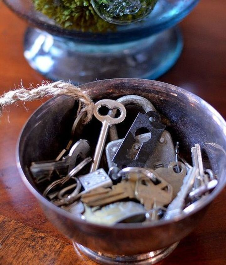 Disgarded keys in a tarnished silver bowl.