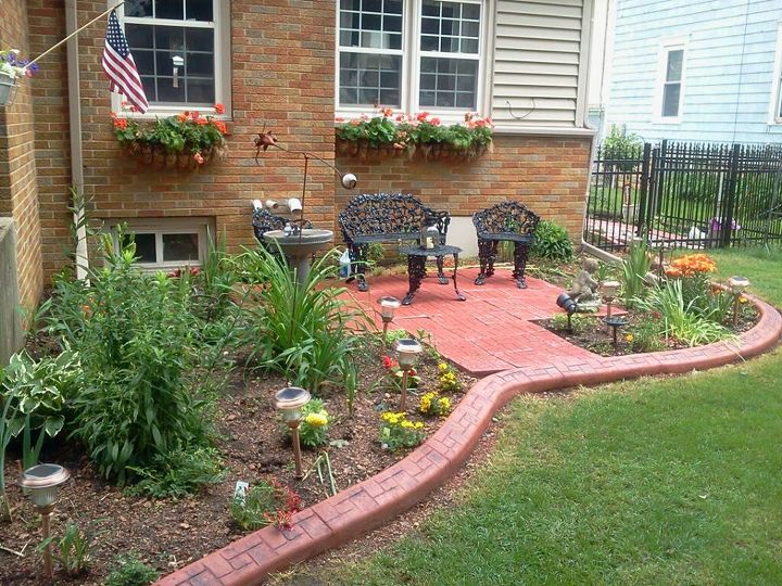 I installed a patio in the front of the house with patio blocks and then had an extruded concrete border put in with a stamped brick design.  I added the plants, the solar-operated bird bath, solar garden lights, and iron furniture.
