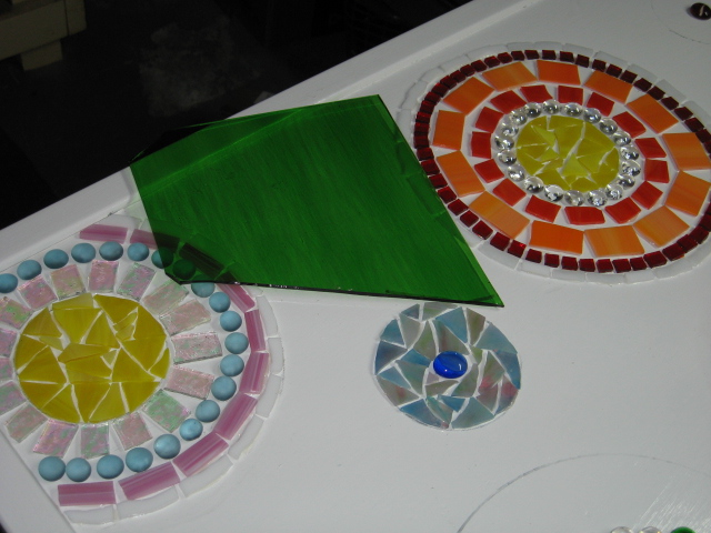 stained glass mosaic patio table, painted furniture, tiling, I made small circles with multicolored glass in between the larger flowers