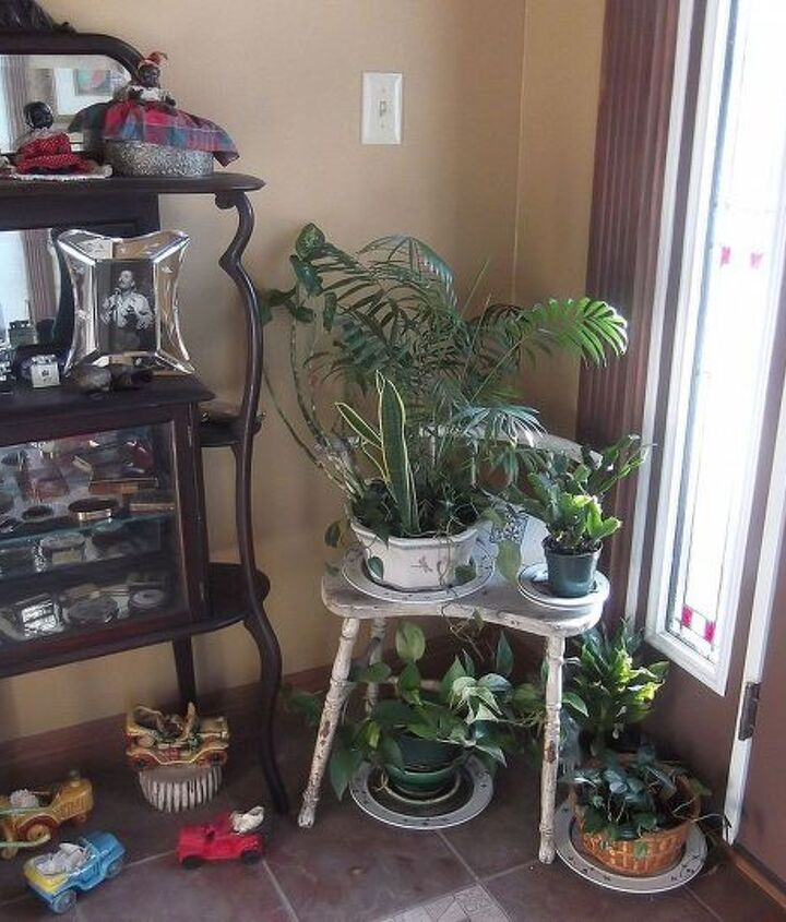 A vintage kidney-shaped bench is a cozy plant stand. her collection of vintage car shape planters add to the charm