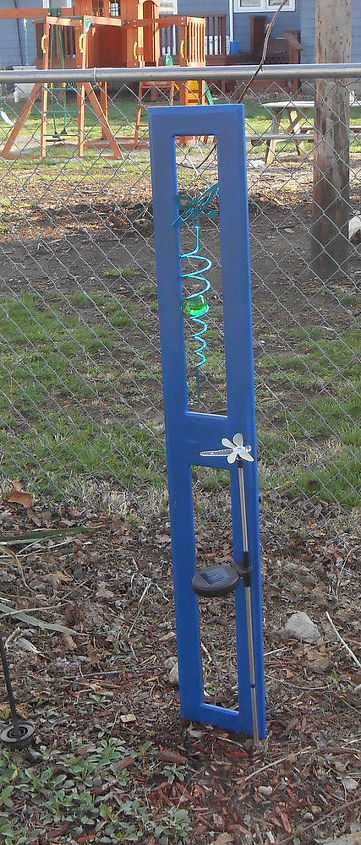 Blue repurposed cupboard door. So easy-some paint, a few clamps and rebar to hold it upright. Decorate it with yard art.