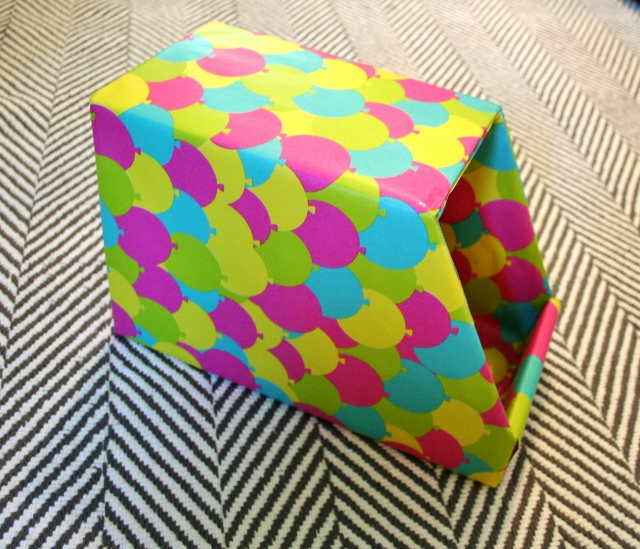 Cut down a cardboard box, cut it with pretty paper, and it's basically a free organization box!