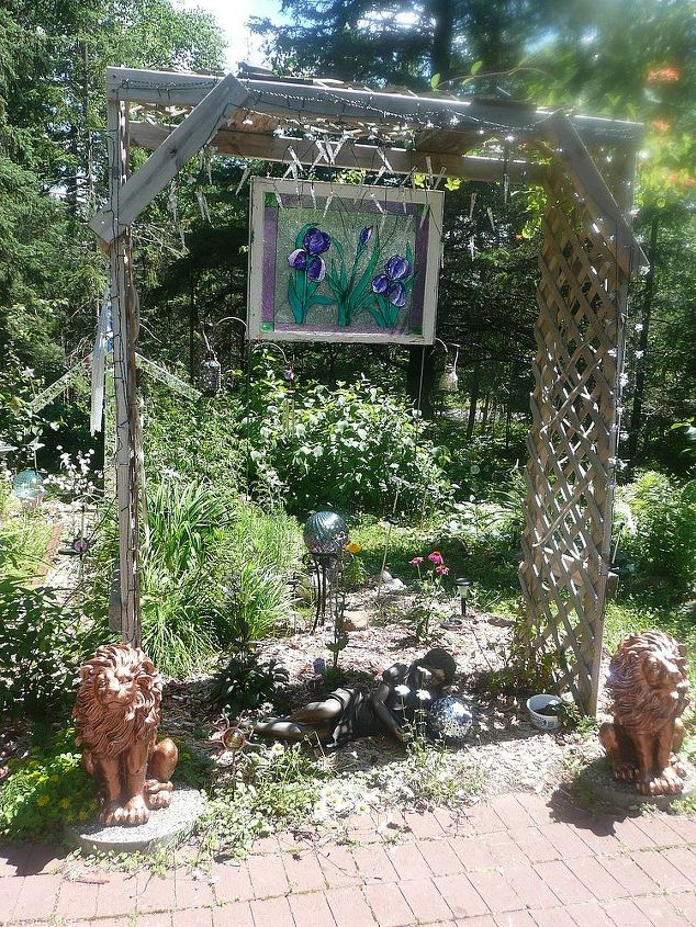 whimsical garden ideas, gardening, My son built this arbor It is covered in purple and white lights The stained glass picture is reflected by the lights at night and shines beautifully in the sun by day