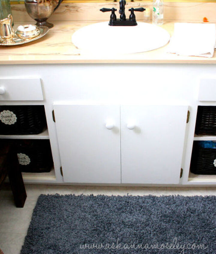 """Removing the cabinet doors and adding baskets gave the space more personality and gives it more of a """"custom"""" look."""
