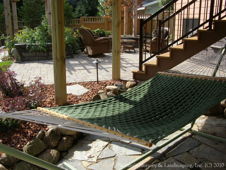 The small boulder wall creates a grade change along with the chilton flagging for the patio create a more relaxed and informal feel to this room under the deck.  The sweet hammock goes along way in making this an awesome oasis.