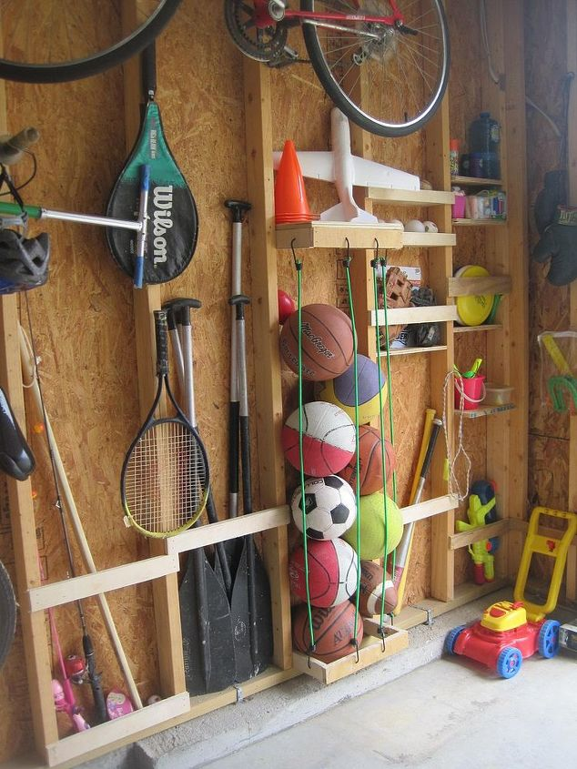 """Nailing slats to the studs provided space to store oars, fishing poles, & baseball bats.  For balls, we nailed a """"U"""" shape (top & bottom), drilled holes, & attached bungee cords into the holes."""
