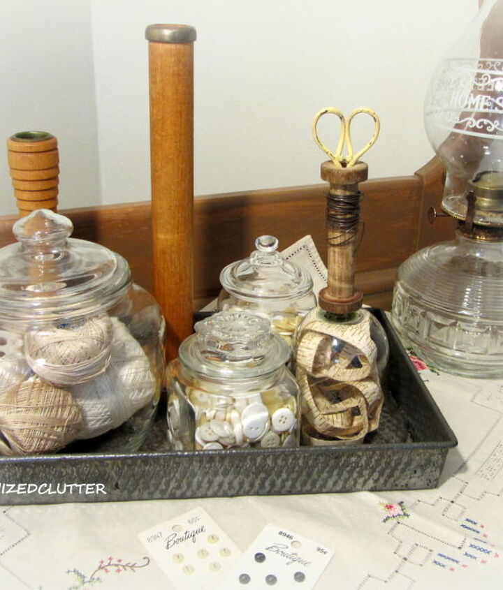 I put together this vignette with buttons, spools, thread, scissors, and a Sears Roebuck vintage measuring tape.  The tape is displayed under the makeshift cloche.
