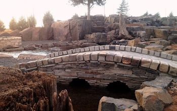 pond bridge, decks, outdoor living, ponds water features, A nice touch to this project that utilized 500 000 pounds of stone to build a pond wetland filter waterfalls fire pit pavilion and stone steps to a remote seating viewing area under the pine beside the cascading water