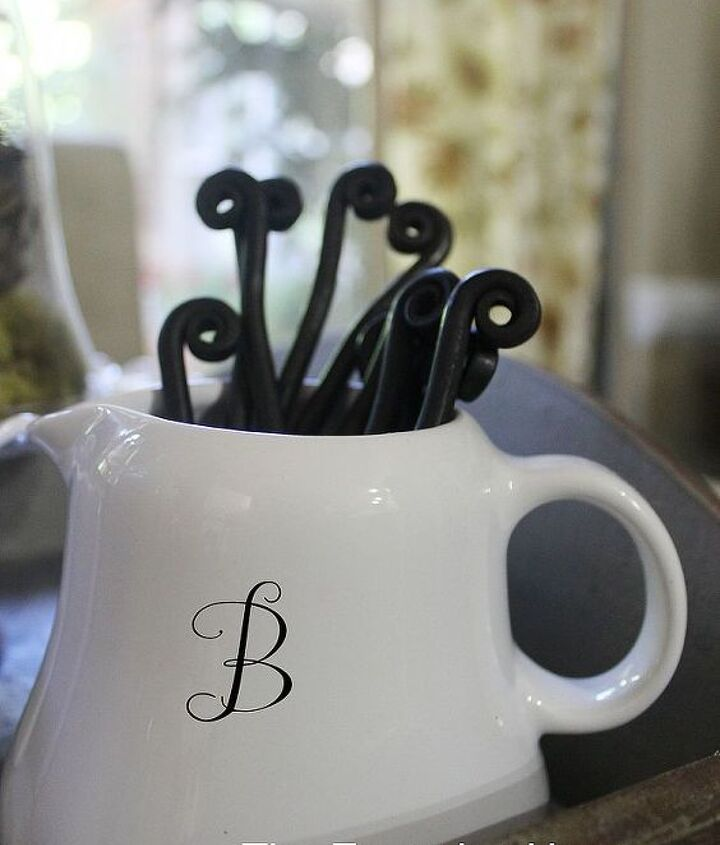 "A small white pitcher with a cute little ""B"" monogram - filled with curly-handled spoons and forks."