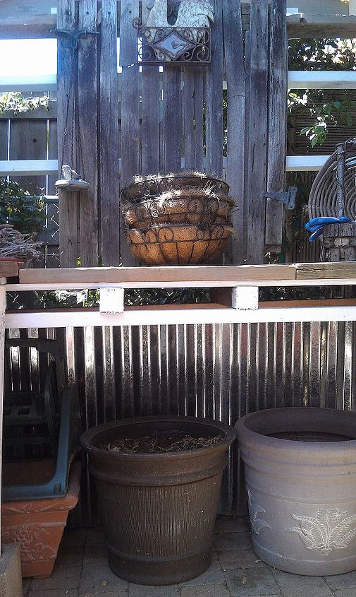 I used these leftover galvanized sheets as a skirt under the table to keep my dogs from going behind it.  The spaces in the pallet above are the perfect size to hold my seed starting trays.  They slide right in.