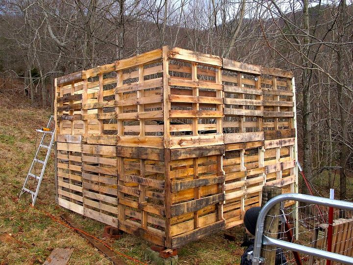 The 2 stories of pallets are secured using the corner posts and recycled wood from around our homestead.