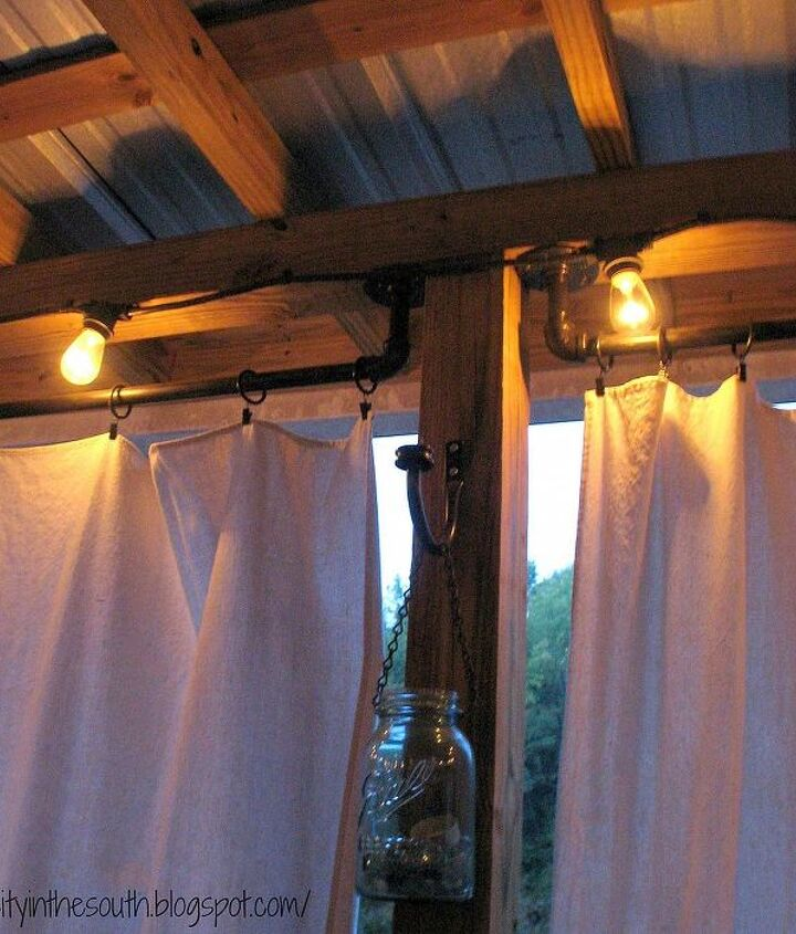DIY curtain rods, string lights, and drop cloth curtains for a covered porch.