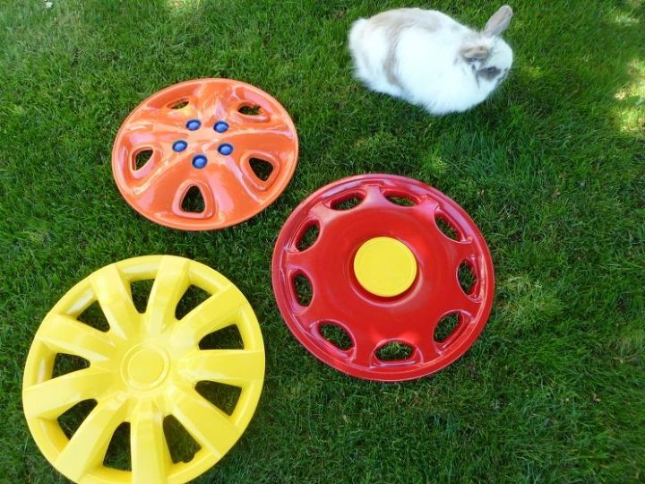 Spray paint hubcaps in fun colors. Use things you have to add interest (spray a plastic lid for the center of a flower, use tongue depressors for a design)