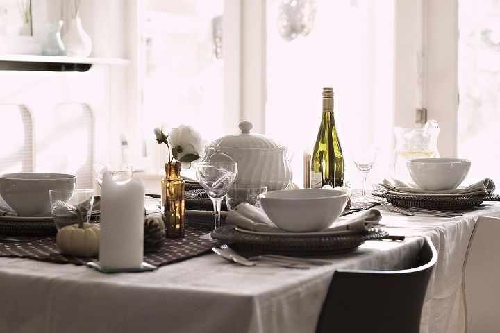 White dishes and candles combine beautifully with the browns in the fabric and the wicker plates.