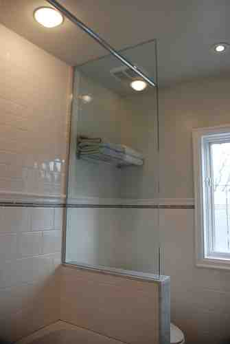 One end of the shower has glass, allowing light in. The small toilet area feels open without a solid wall closing it in.