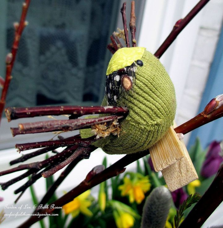 little green fabric bird with twigs for a beak, wings & tail
