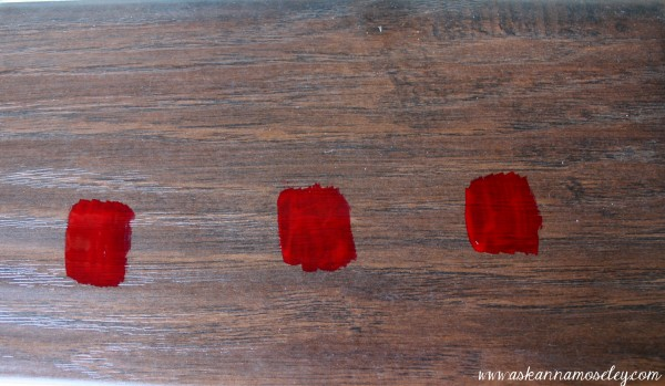 I painted three swatches of bright red polish on a scrap of flooring to see which product would take it off.