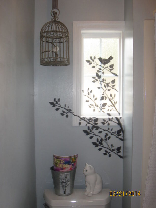 Painted walls gray, stenciled black tree and bird across window and wall.  Painted trim bright white. Bird cage hung with silk ribbon from a Christmas present, realistic bird, bird's perch is a branch from our woods.