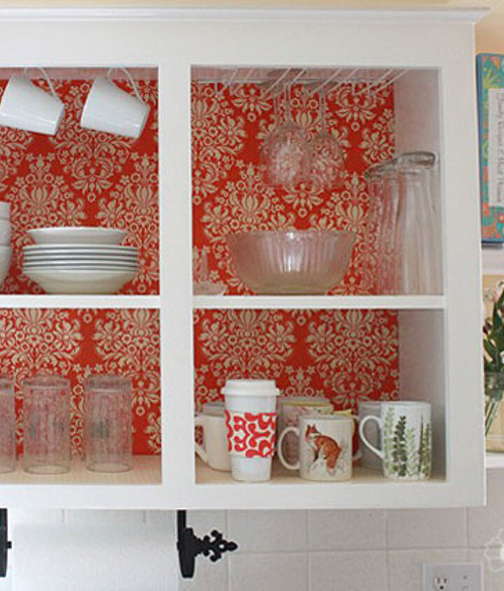 Open kitchen cabinet with cup hooks for coffee mugs.