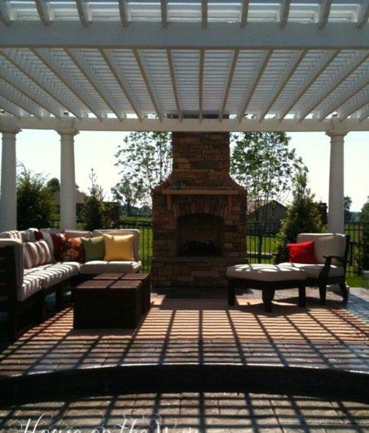 Pergola and outdoor chimney with outdoor sectional and all weather wicker coffee tables.