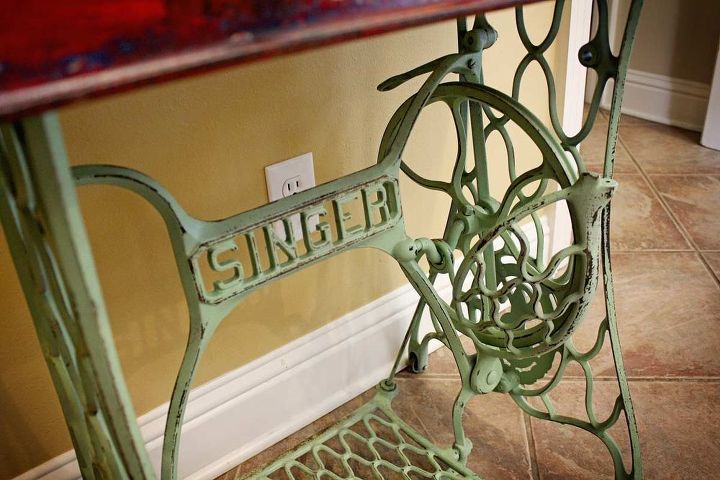 An antique Singer sewing machine base with distressed green paint serves as a solid base.  Repurposed Red Wagon Sewing Machine Base Storage Table by GadgetSponge