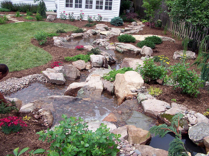 In the backyard, a pondless waterfall is turned into a twisting, turning stream.