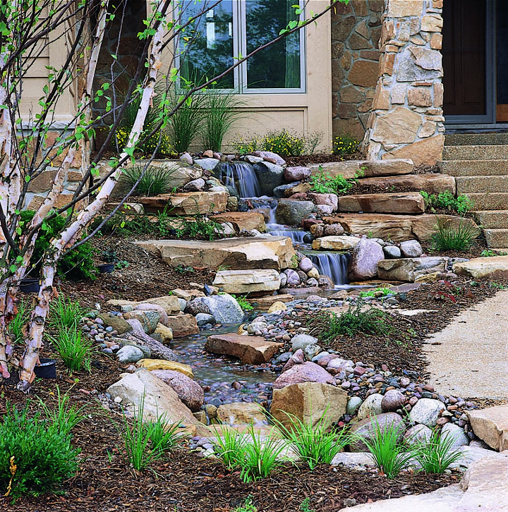 The home's front entrance showcases a beautiful, re-circulating pondless waterfall.
