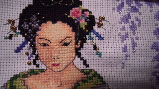 q anyone cross stitch out there need help with finished project, crafts, reupholster, Close up of the head which contains many beads both purple gold