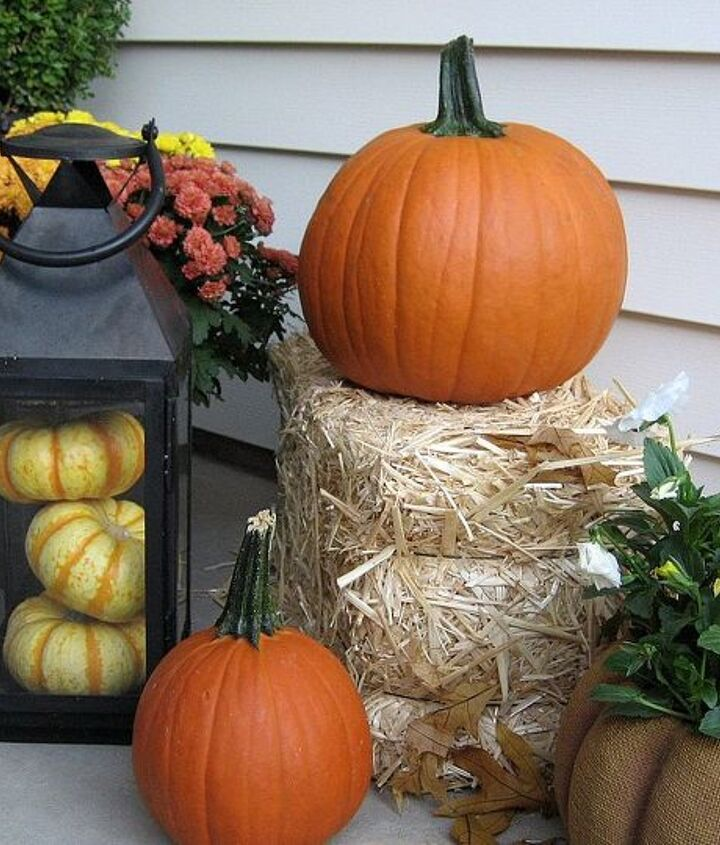 Traditional pumpkins,pansies and mums plus a lantern filled with tiger pumpkins line one side of the porch