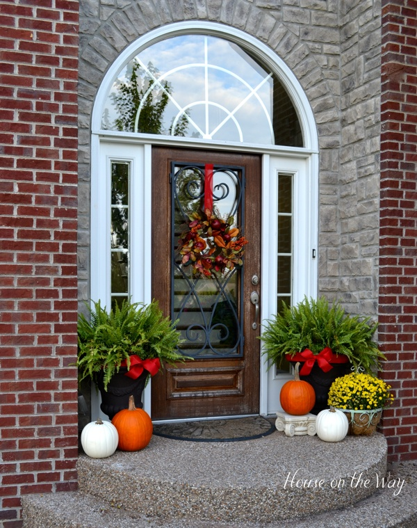 This is the main entrance to my home. My ferns were still beautiful, so I decided to continue to use them at the door. I added some red burlap ribbon to the planters and brought in some fall colors with pumpkins and mums.